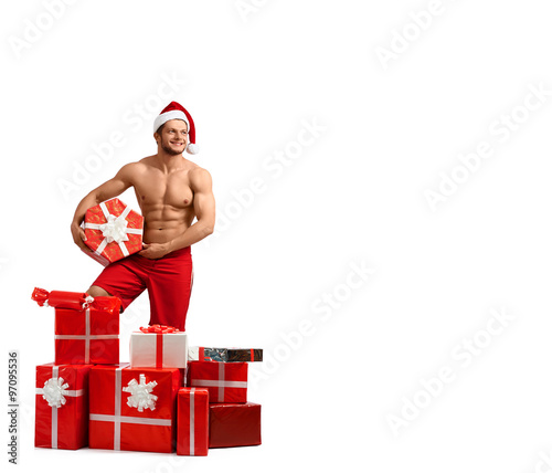 4b51ebd19f4e5 Horizontal fulllenght shot of a naked ripped man wearing Santa hat looking  away with a gift box in his hands