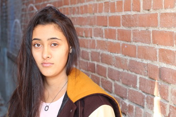 Portrait close up of young beautiful ethnic girl on brick wall background with copy space on the right side