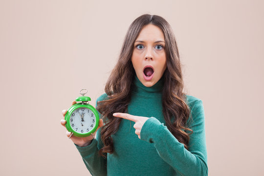 Woman holding clock that shows five to twelve time