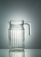 Glass jar with reflection on illuminated white background
