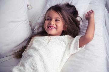 Happy little girl lying in bed