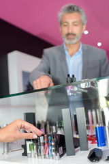 Man pointing to electronic cigarette through glass counter