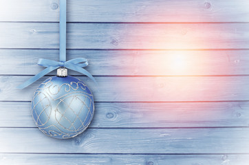 Blue Christmas baubles with curly ribbon on a blue; sunny wooden