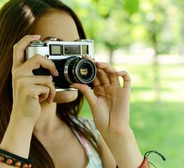 Girl taking photo with retro soviet no name camera outdoor, imag