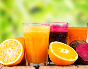 Fresh juice, mix fruits and vegetable, carrot, beetroot and orange drinks on wooden table.