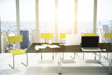 Blank laptop creen on black table in modern office with city vie