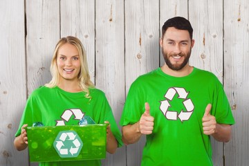 Composite image of cheerful volunteers with recycling bin
