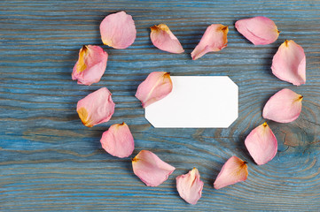 Pink rose petals imaging heart shape on blue wooden board with blank white card inside