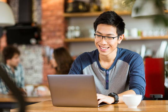 Happy cheerful asian male smiling and using laptop in cafe
