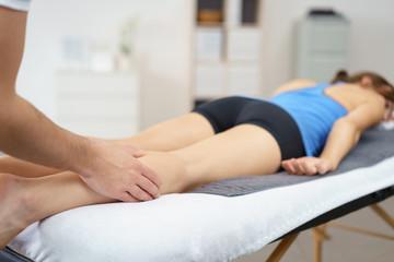 physiotherapeut behandelt die wade einer patientin