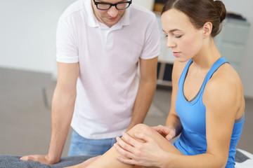 frau spricht mit einem physiotherapeuten über die schmerzen im kniegelenk