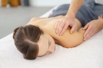 therapeut behandelt eine patientin mit schmerzen an der schulter