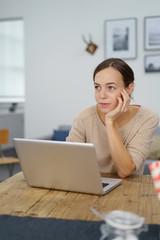 junge frau sitzt zuhause vor dem laptop und grübelt