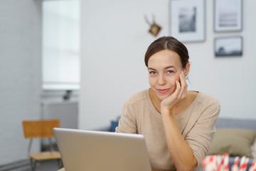 lächelnde junge frau mit laptop in ihrer wohnung