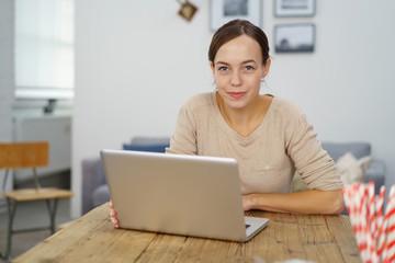 moderne junge frau sitzt in ihrer wohnung und arbeitet am laptop