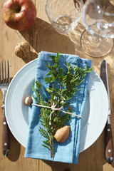 Place setting decor with evergreen plants, nuts and apple