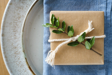 Detail of place setting decor: simply wrapped present decorated with green branch and twine on the blue napkin