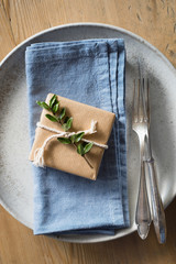 Place setting decor: simply wrapped present decorated with evergreen branch and twine on the blue napkin