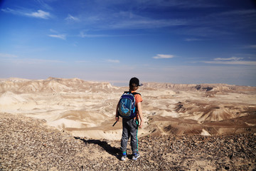 Cute 8 years old boy hiking in the desert