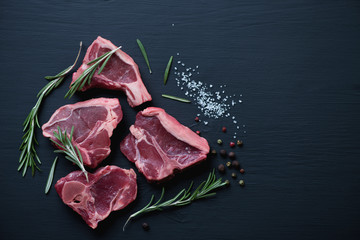 Top view of raw T-bone lamb steaks on a black wooden surface