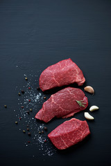 Deurstickers Vlees Marbled beef steaks with seasonings on a black wooden surface