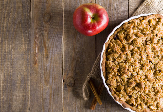 Pie with crumble on plank background. Apple crumble. Apple pie with crumble on wooden background.