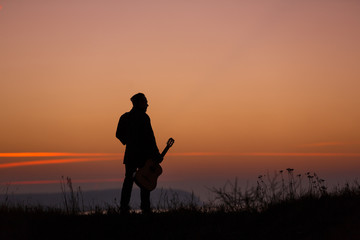 Man with guitar in sunset