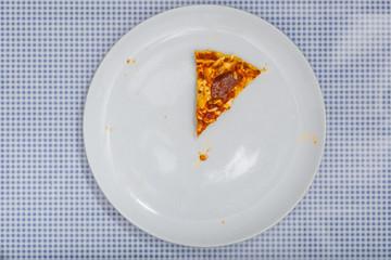 Letztes Stück von Pizza Salami, auf blau kariertem Untergrund,