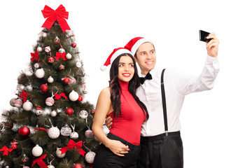 Couple taking a selfie by a Christmas tree