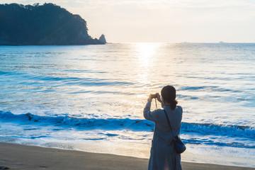 浜辺で写真を撮る女性