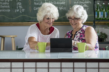 Senior women sharing an ipad/tablet at a cafe