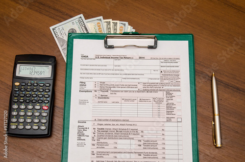 1040 tax return form with calculator on wodden background for 1040 tax table calculator