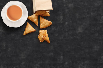 Tea/chai served along with crisp samosas, a local snack