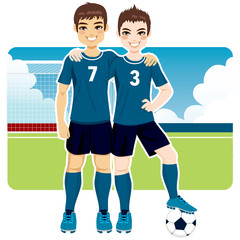 Two soccer team friends in uniform standing on field
