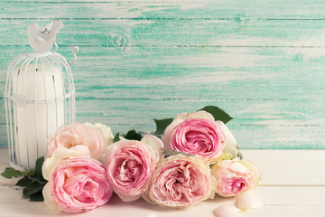 Fresh pink roses and candle in bird cage