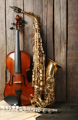 Musical instruments: saxophone, violin and flute with notes on wooden background