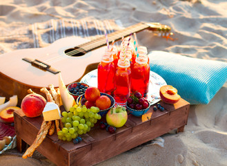 Foto op Plexiglas Picknick Picnic on the beach at sunset in the boho style