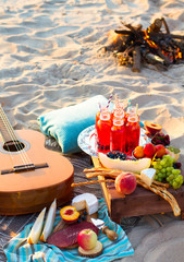 Picnic on the beach at sunset in the boho style