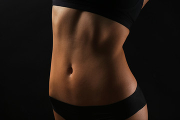 Slim female body in nice black lingerie on dark background