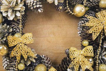 Christmas wreath of cones and balls on wooden surface.