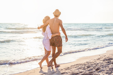 Sunset, sandy beach, a loving couple walks embraced on the deserted beach at sunset during a day at the beach on vacation
