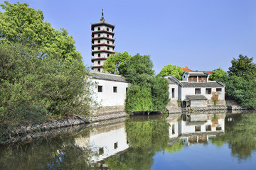Traditional white Chinese house and pagoda reflected in a tranquil canal.