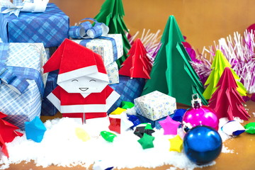 Santa claus and gift box with small star paper on the snow field