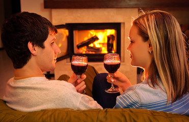 Happy young couple sitting near fireplace and drinking wine