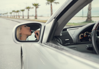 Woman apply  lipstick looking in rear view car mirror