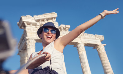 Happy smiling young woman take a selfie photo on antique sights