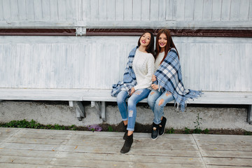 Two girls sit on a bench in the park