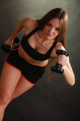 Fit woman exercising with dumbbells.