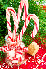 Bunch striped candy canes in glass jar on christmas background