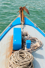 Rusty anchor on the front of a blue wooden boat